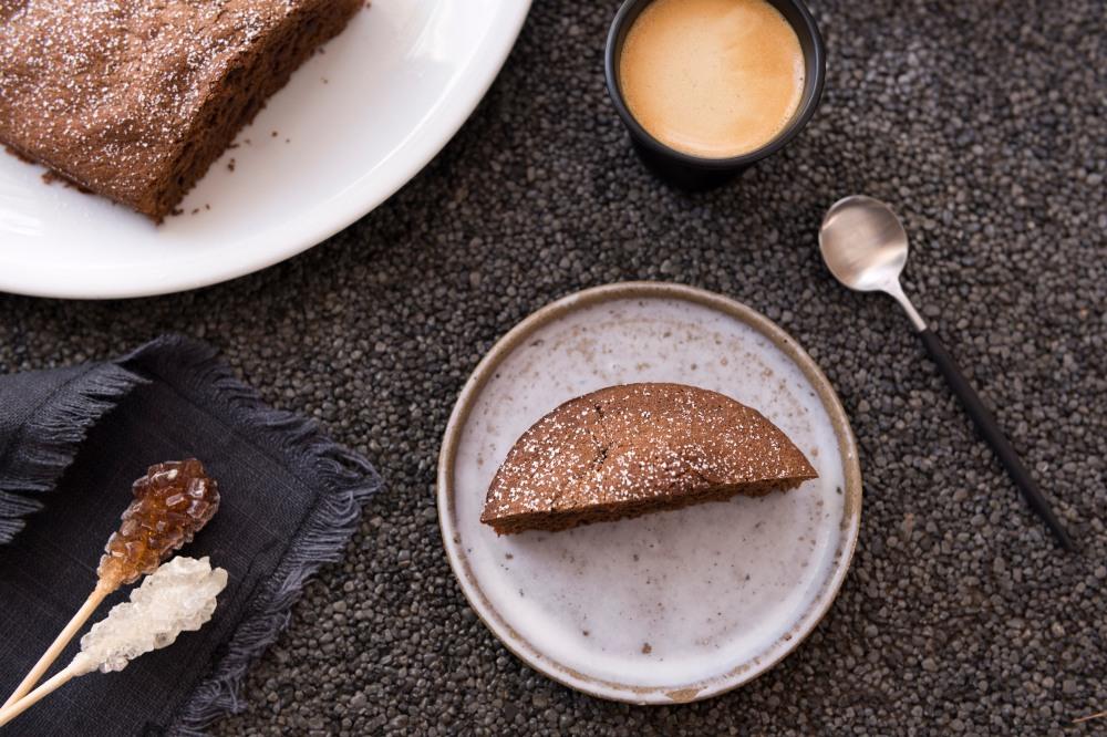 Photo vue du dessus d'une tasse de café, une petite assiette avec une part de gateau au chocolat, une cuillère, et dans l'angle en haut à gauche une assiette avec le gateau au chocolat