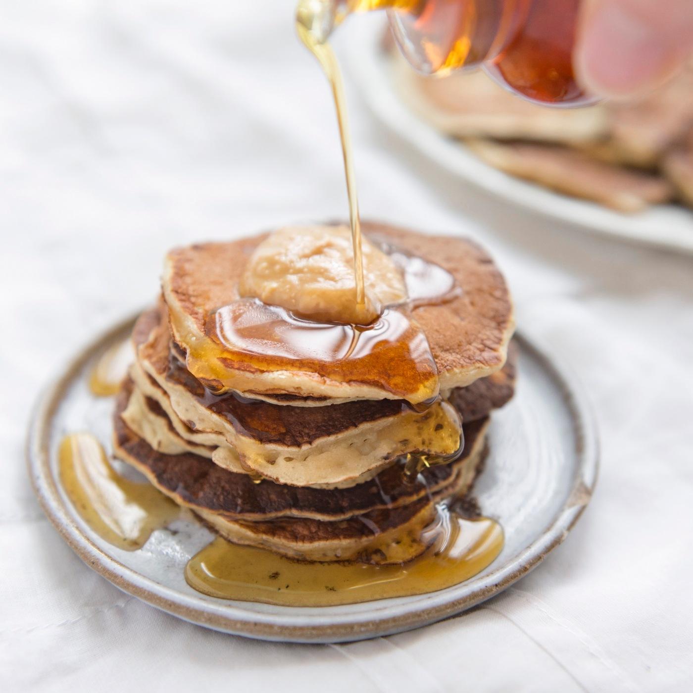 Photo du dessus d'une pile de pancakes avec sirop d'érable et beurre de cacahuète.