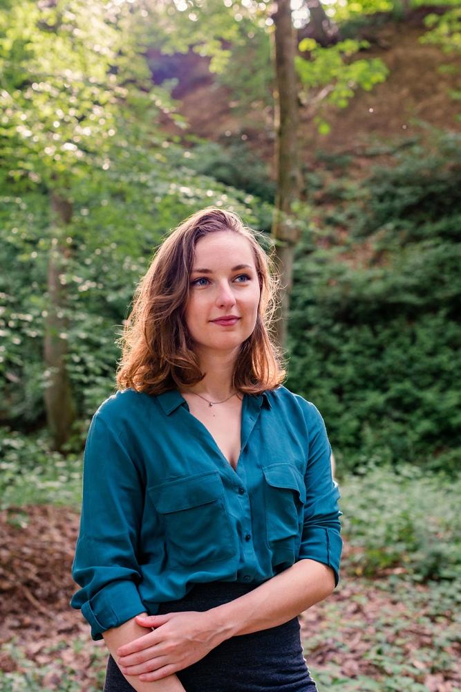 Portrait d'une femme avec la lumière dans les cheveux, dans la forêt.