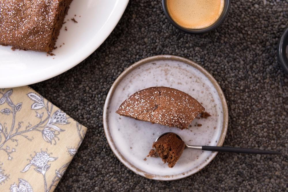 Photo vue du dessus d'une tasse de café, une petite assiette avec une part de gateau au chocolat et un morceau dans une cuillère et dans l'angle en haut à gauche une assiette avec le gateau au chocolat