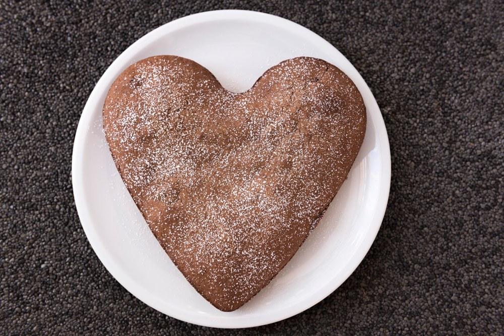 Photo vue du dessus d'un gâteau au chocolat en forme de coeur saupoudré de sucre glace dans une assiette blanche
