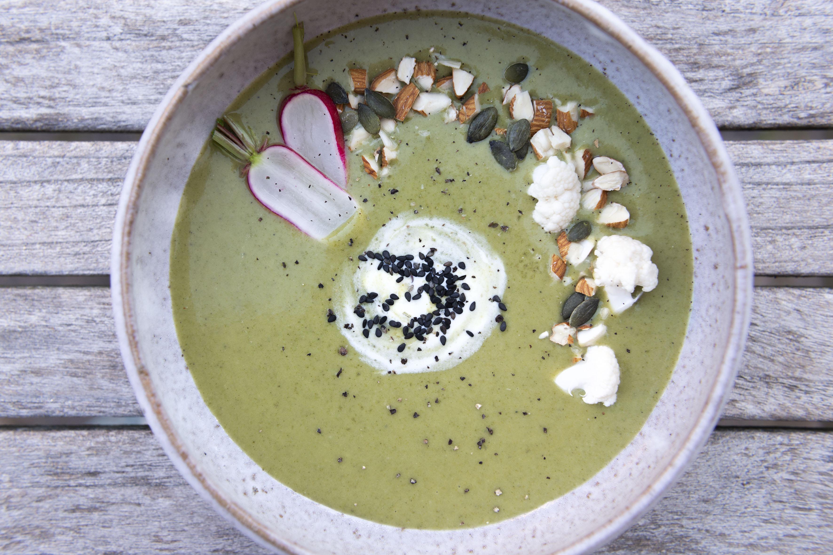 Photo vue du dessus d'un velouté vert parsemé de graines, légumes crus, amandes effilées... dressé sur assiette creuse grise.