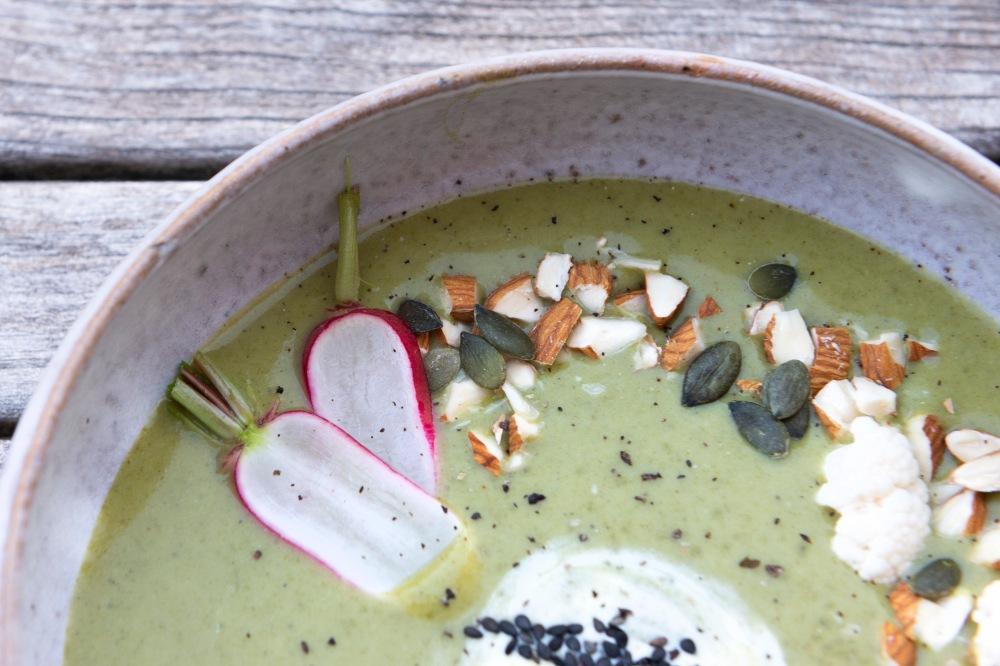 Gros plan sur le dressage de la soupe verte parsemée d'amandes concassées, de graines de courges, de fleurettes de choux fleurs et de lamelles de radis.