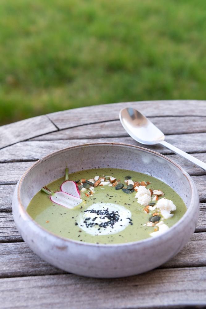 Photo de face d'une assiette creuse remplie d'un velouté vert, posée sur une table en bois avec une cuillère à soupe.