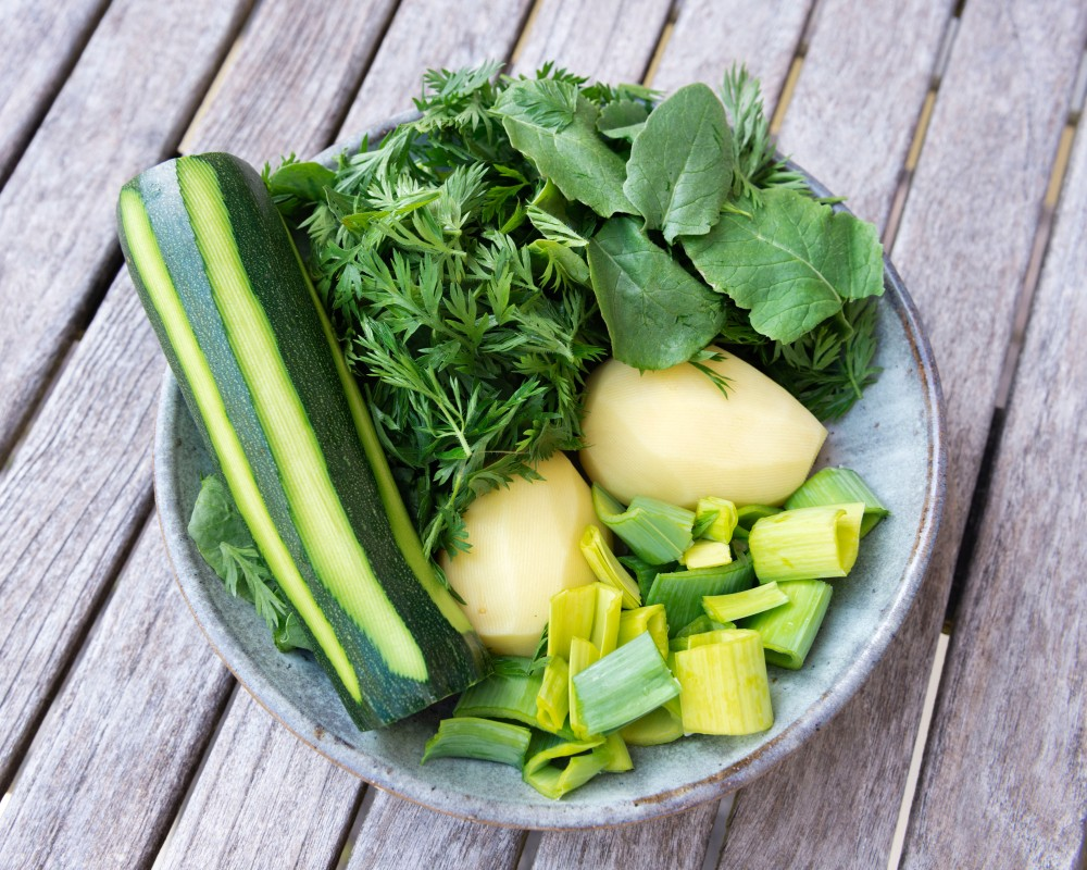 Assiette vue du dessus avec une courgette crue, des fanes de carottes, des fanes de radis, deux pommes de terre et du vert de poireau en lamelles.