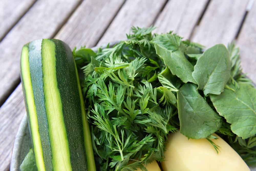 Zoom sur une assiette de légumes crus : une courgette, des fanes de carottes et de radis, deux pommes de terre.